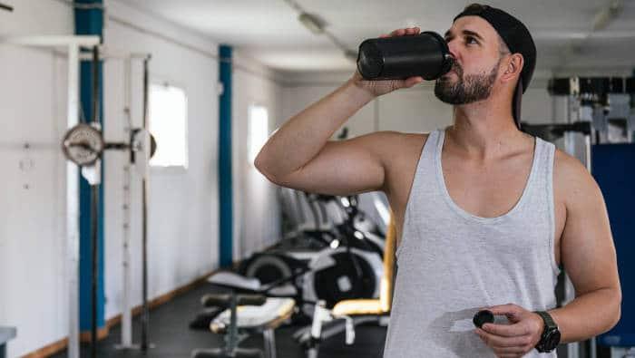 Fitnesssportler trinkt Eiweiß für den Muskelaufbau