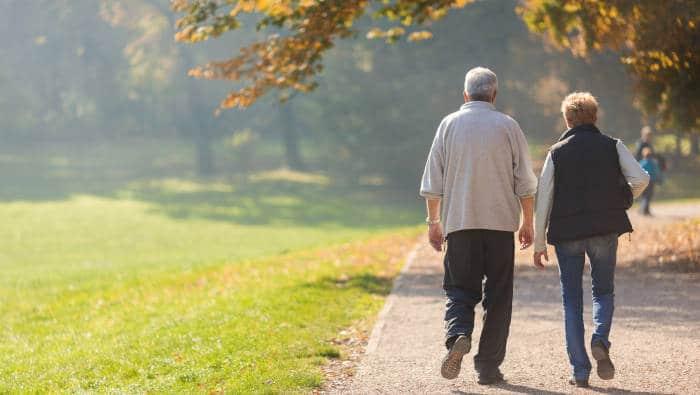 Zwei ältere Menschen halten sich mit Spazieren fit